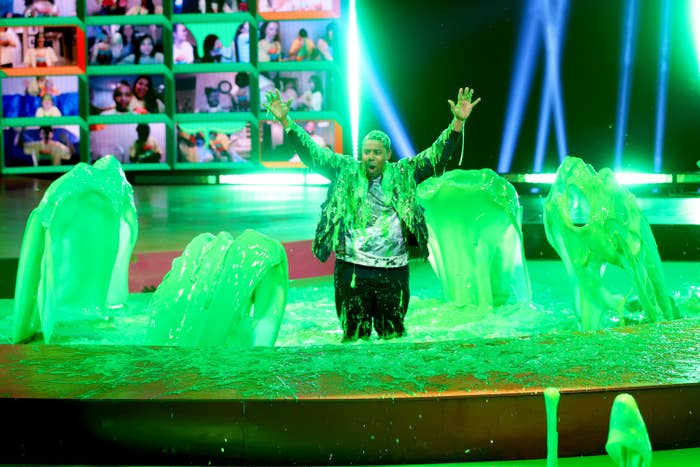 Host Kenan Thompson stands in a pool of slime