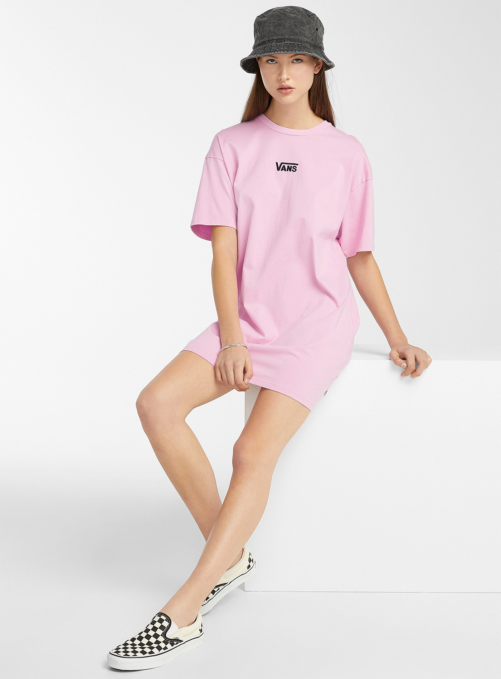 A person wearing a T-shirt dress with Vans shoes