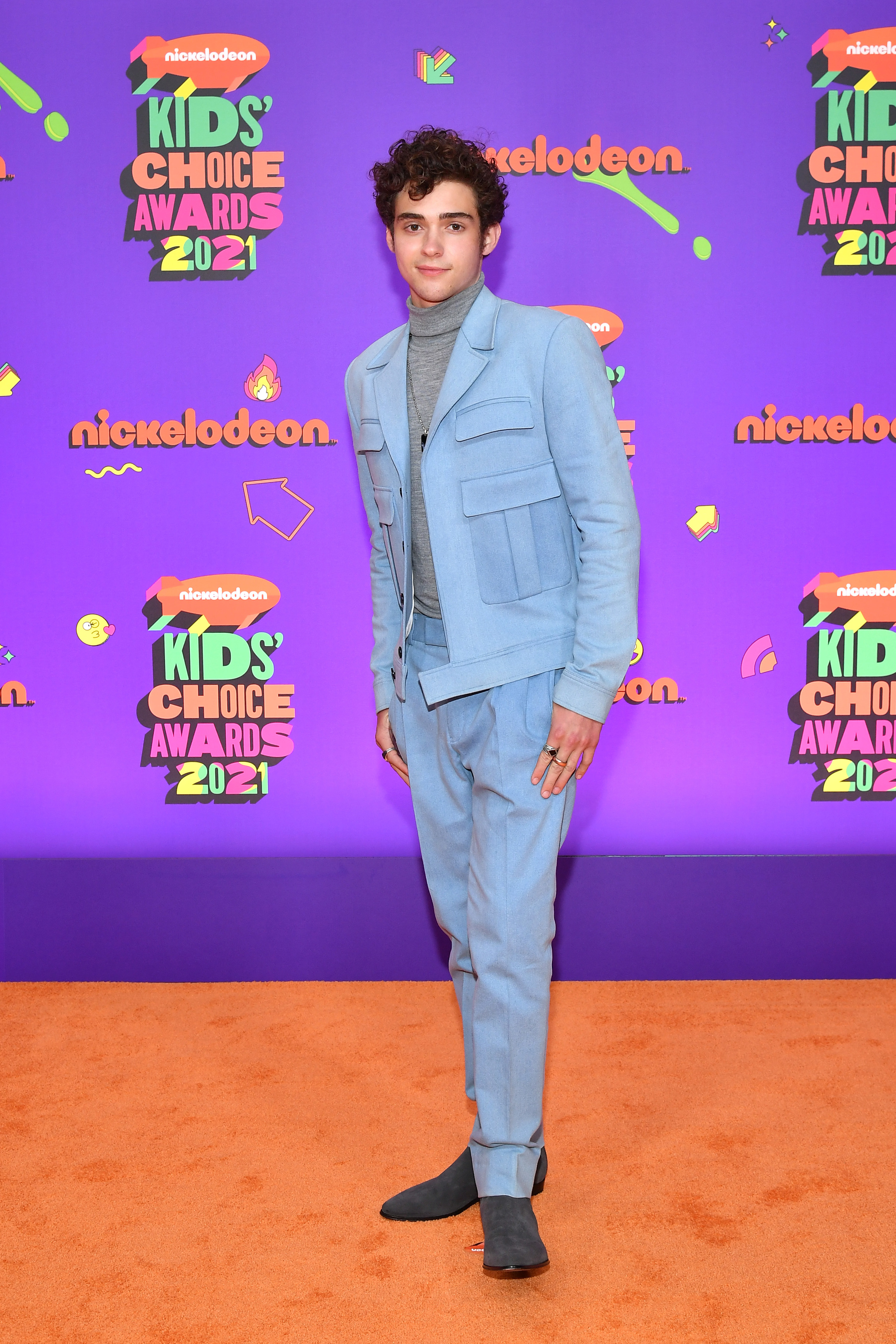Joshua in a powder blue suit pants with a modern jacket with large pockets