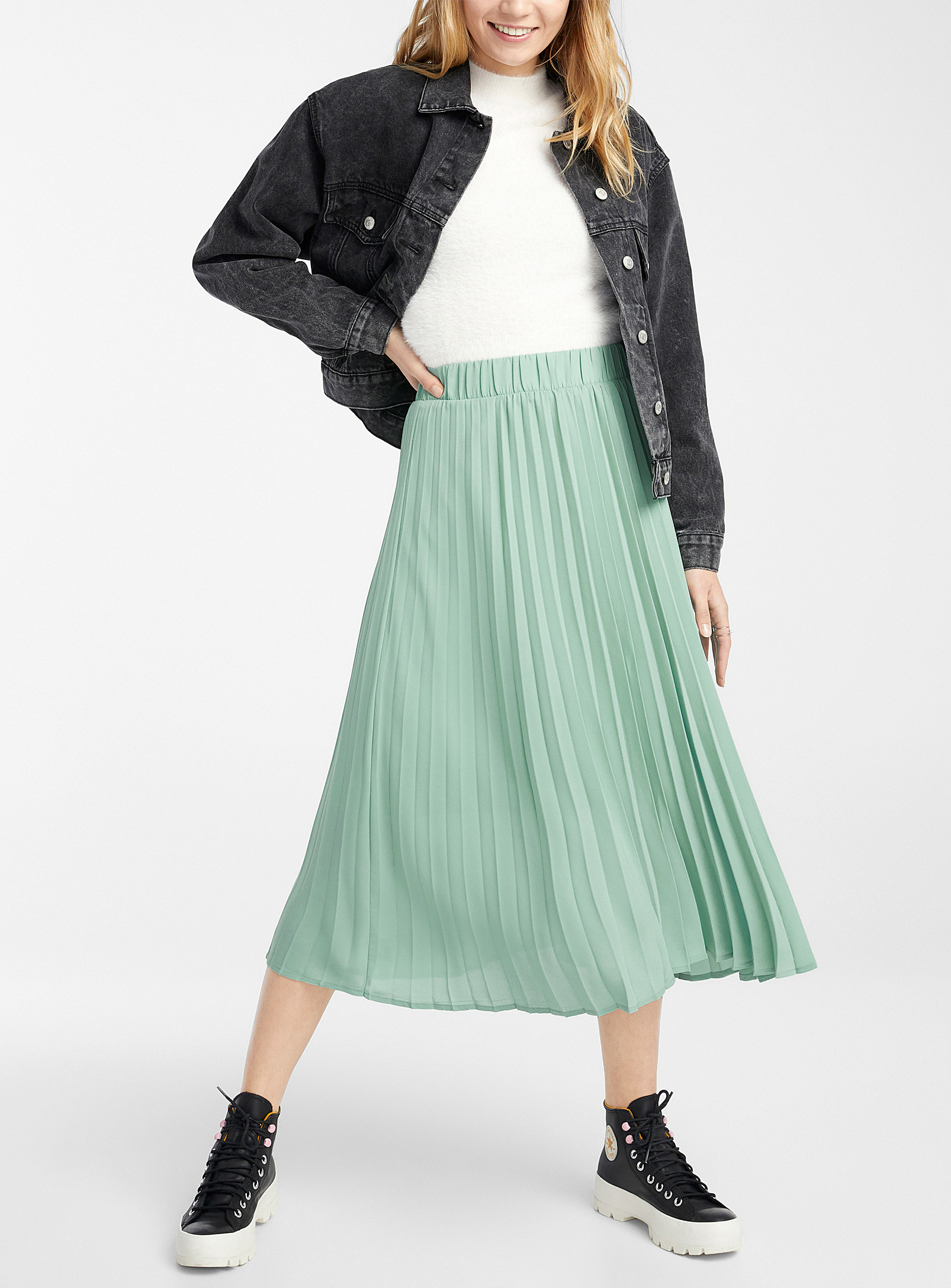 A person waring a long pleated skirt with combat boots