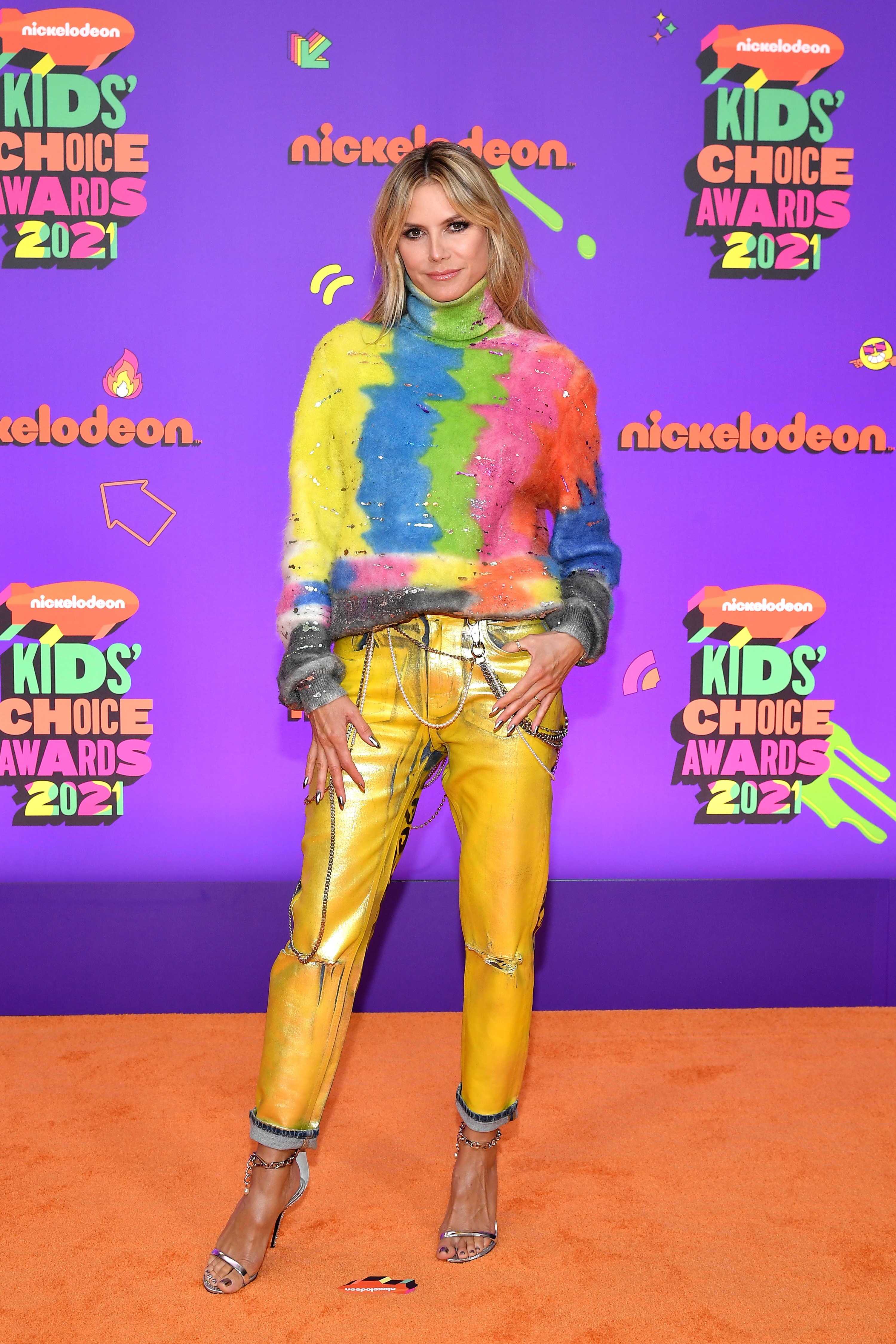 Heidi in a tie-dye turtleneck sweater and yellow jeans