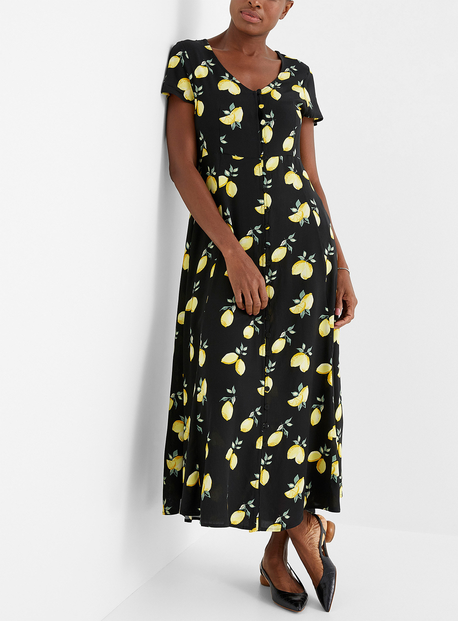 A person wearing a long dress with a lemon pattern