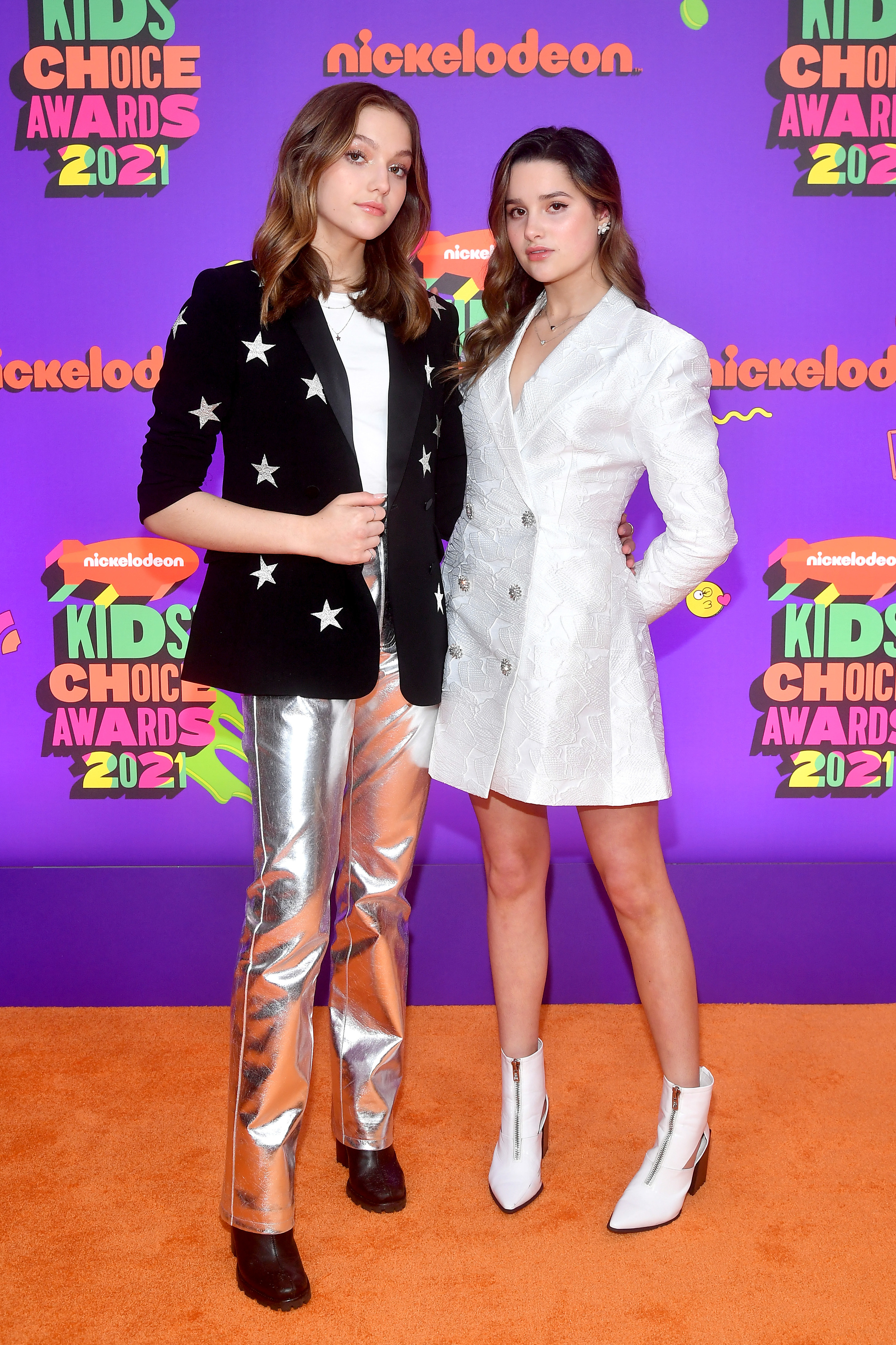 Jayden in metallic silver jeans and a black blazer with yellow stars and Jules in a white blazer dress