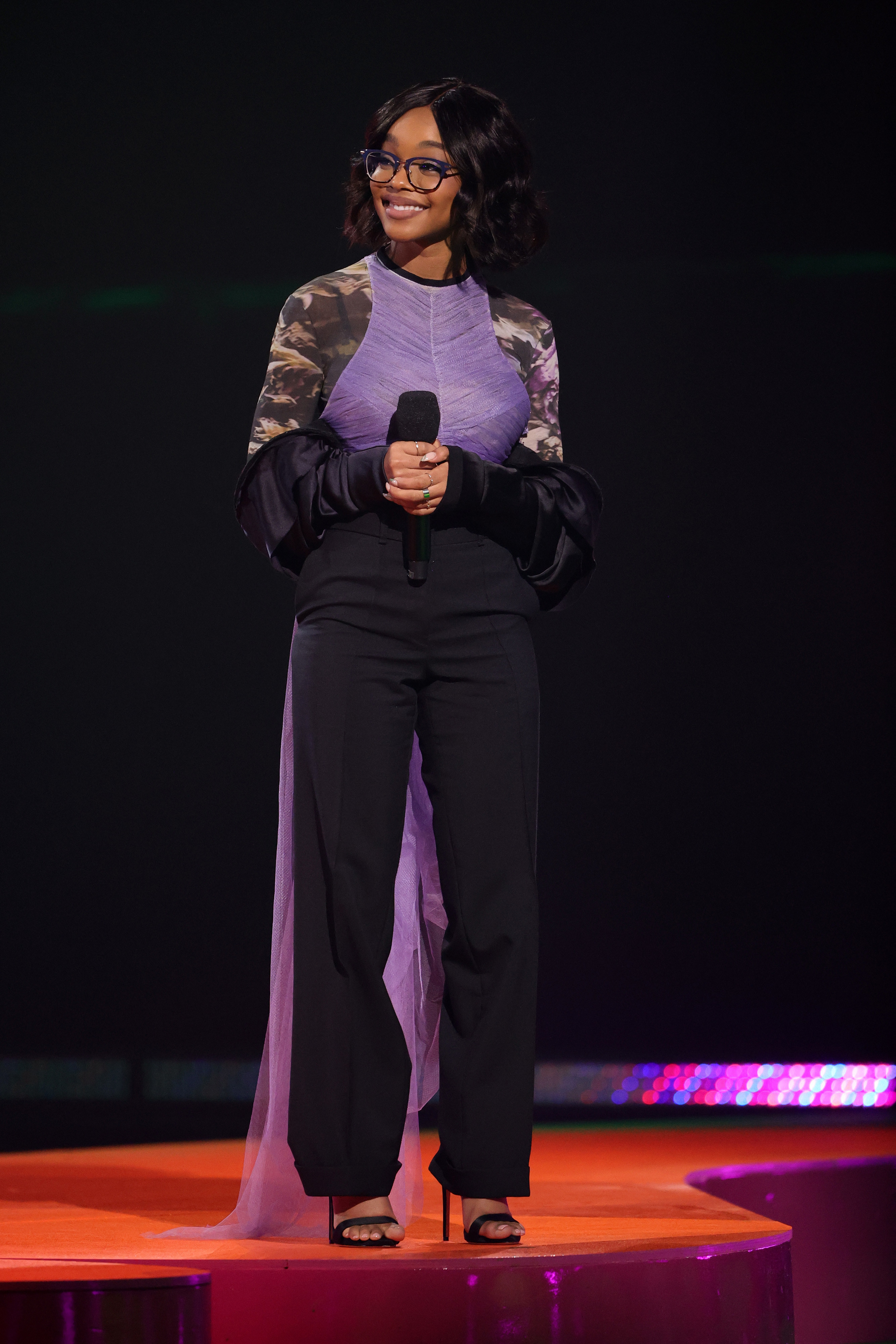 Bespectacled Marsai smiling and wearing high heels, black pants, and a top with flowy sleeves and a purple train