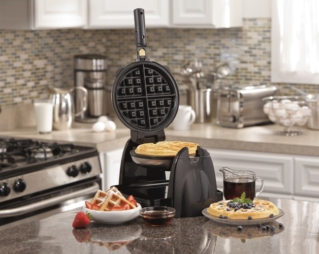 the black appliance cooking a waffle