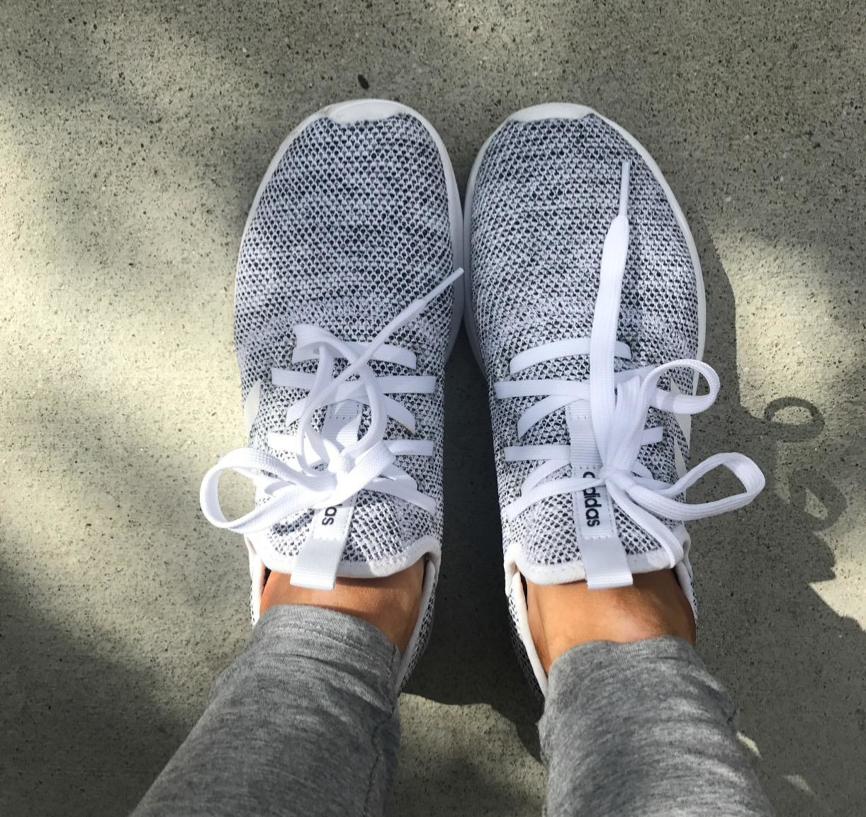 reviewer wearing black and white adidas running shoes with white shoelaces