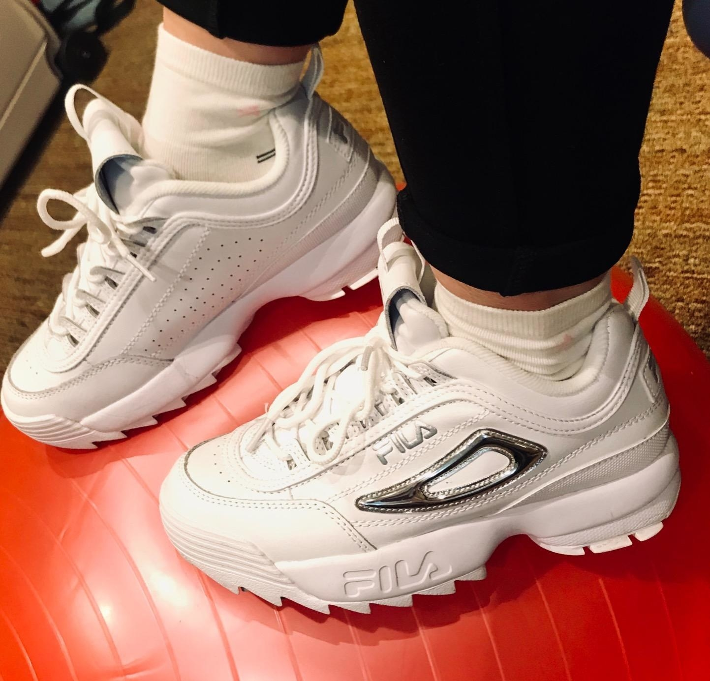 reviewer wearing chunky white fila sneakers