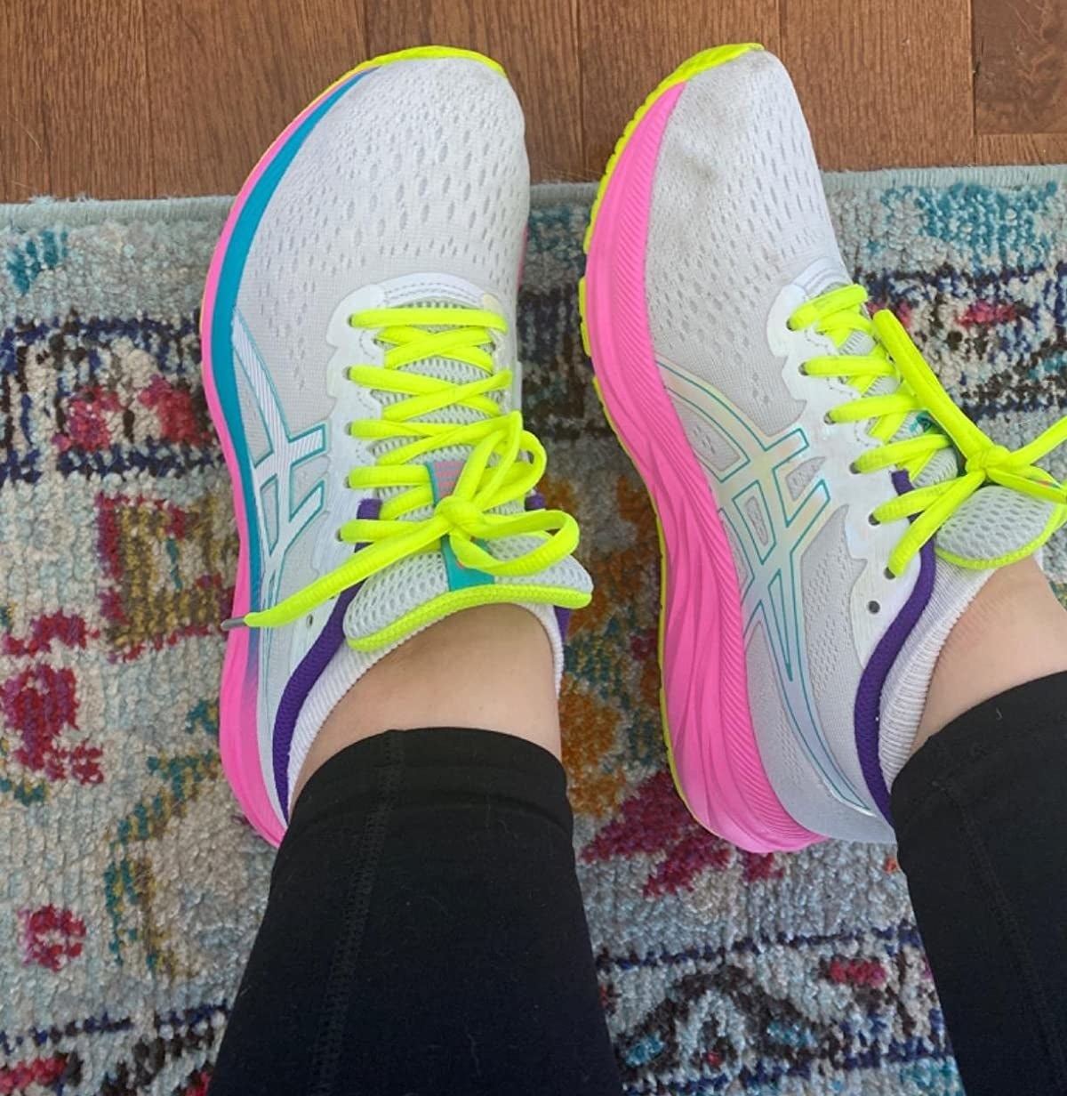 reviewer wearing white asics sneakers with fluorescent yellow laces and hot pink soles
