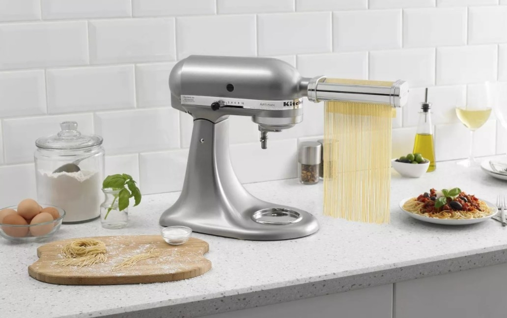 A pasta rolling attachment shown in the front of the stand mixer