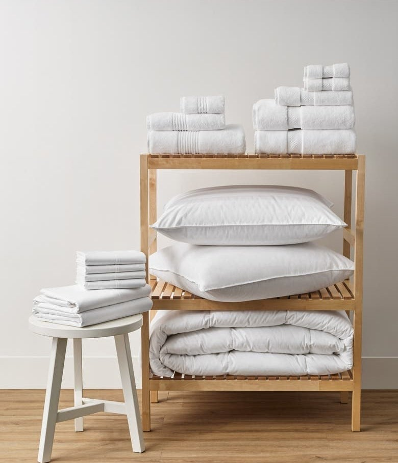 White towels with sheets, pillows and a comforter on a light wood stand
