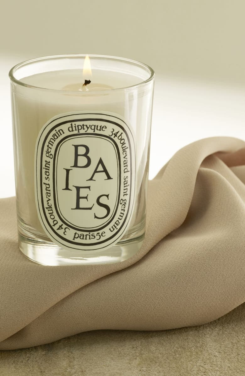 Baies diptyque candle on a cream blanket with a black and white label