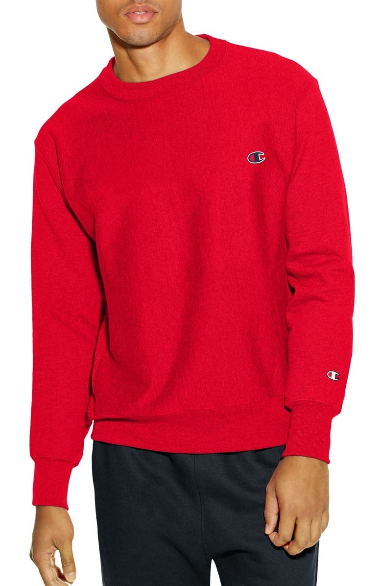 Model wears the red champion sweatshirt with black sweatpants