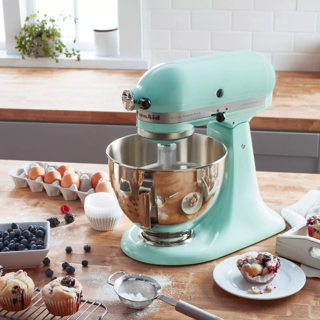 A teal blue stand mixer with paddle attachment and silver mixing bowl