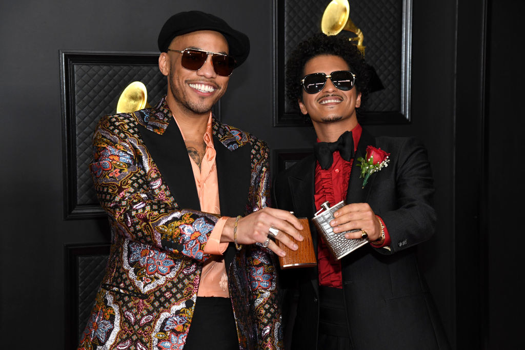Anderson and Bruno smiling on the red carpet and holding flasks
