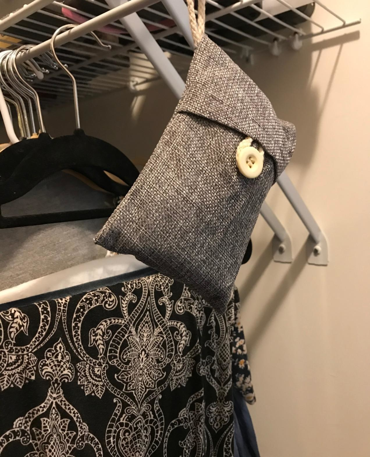 one of the small gray bags hanging in a closet