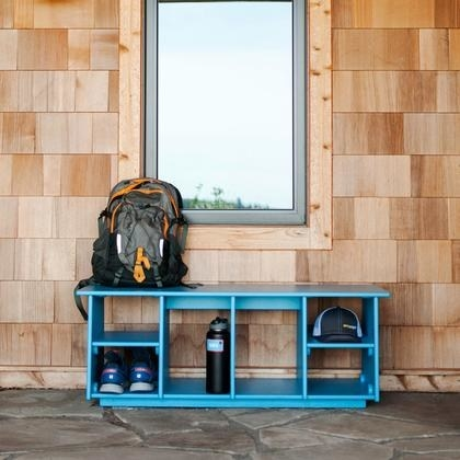 side of a house with a colorful bench that has various size storage cubbies underneath