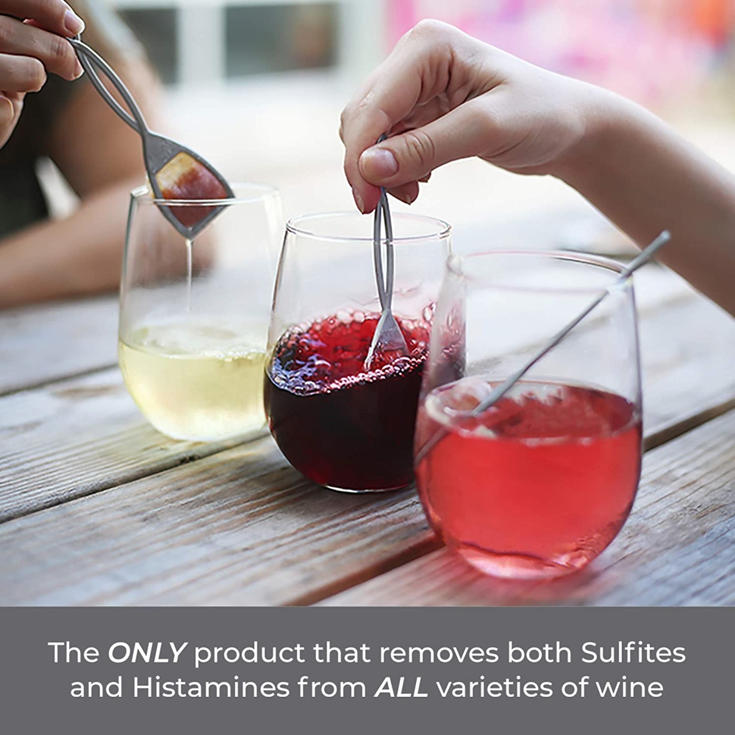 people using handheld wands to swirl in wine glasses