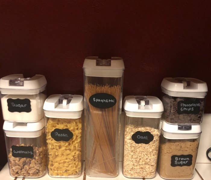 The reviewer's photo of the seven-piece storage container set in a cabinet
