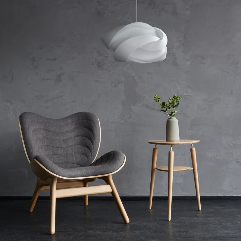 the white pendant light hanging over a chair and side table