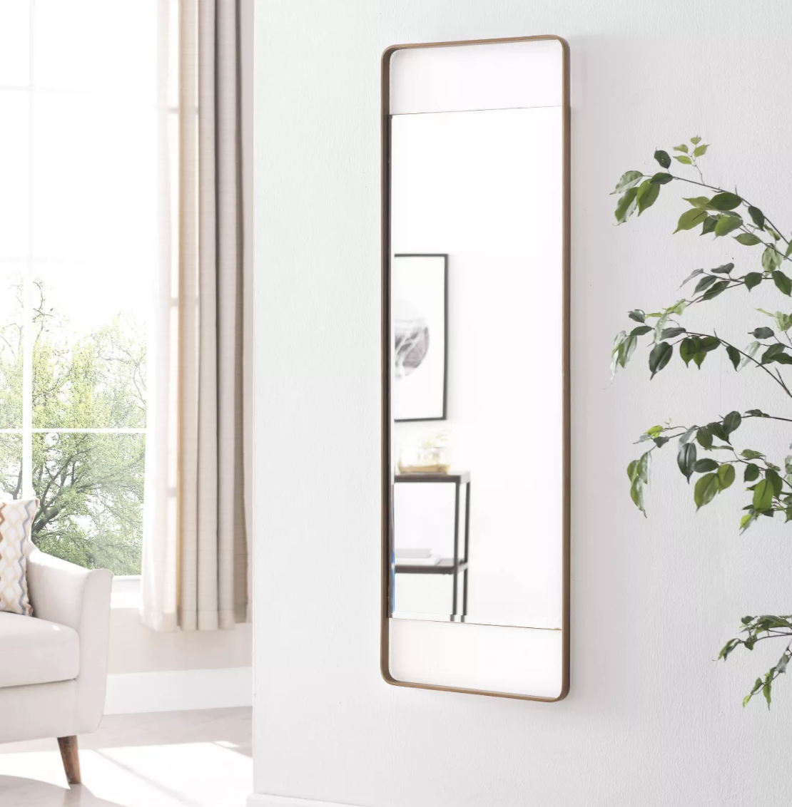 the gold-framed mirror mounted on a wall