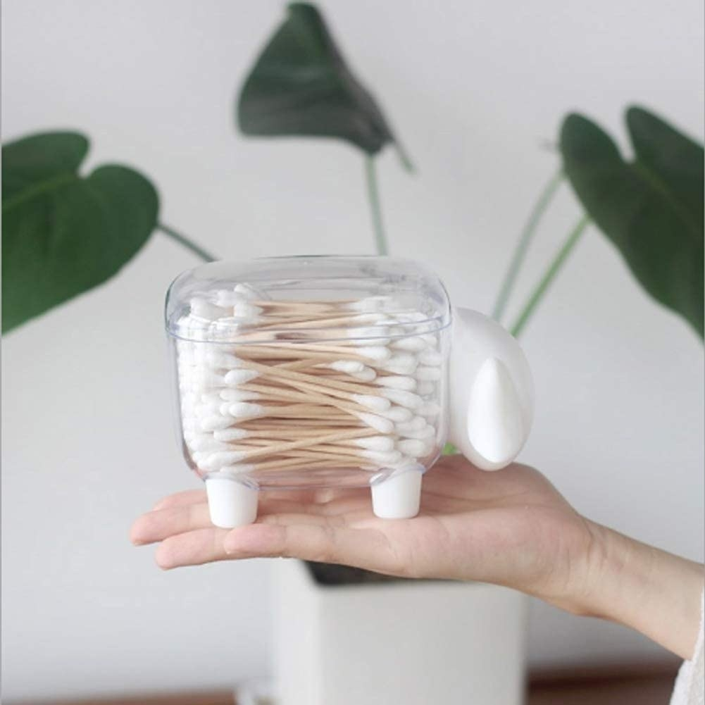 A person holding the sheep-shaped container filled with cotton swabs
