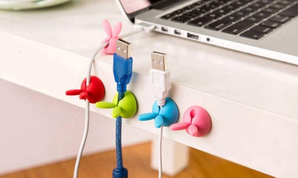 four bunny ear cable clips on the side of a desk