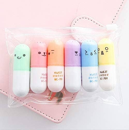 six pill-shaped highlighters with cute faces on the lids
