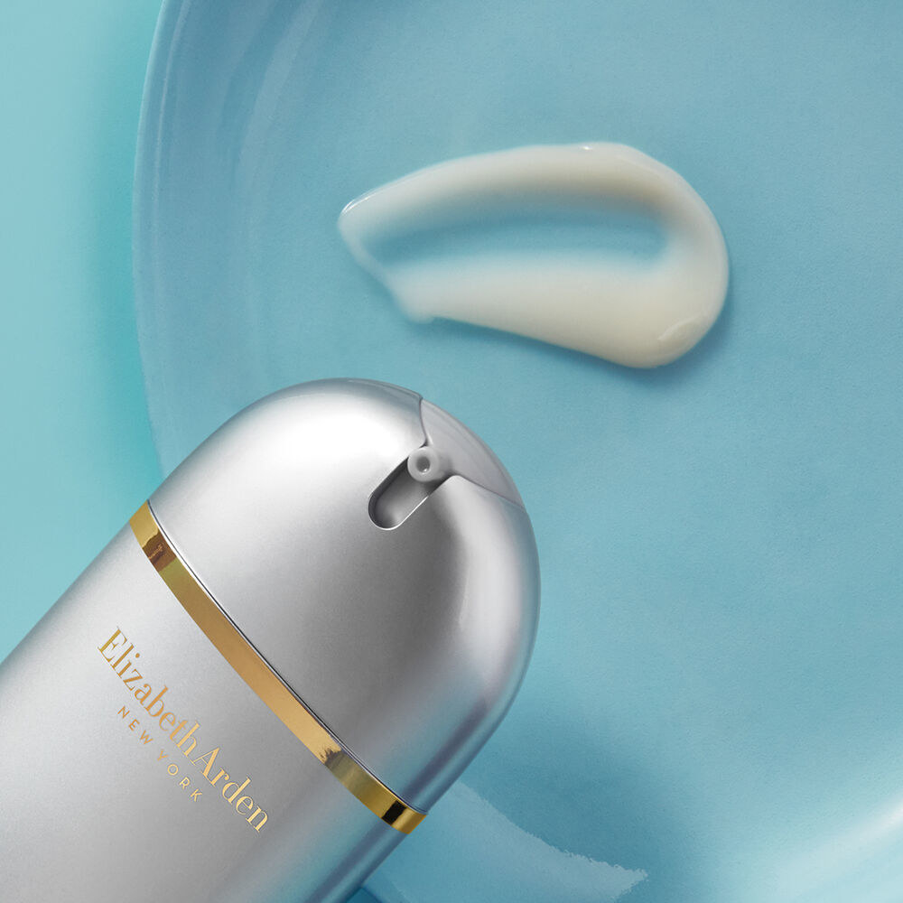 the Skin Renewal Booster in a silver and gold bottle squirting out white formula