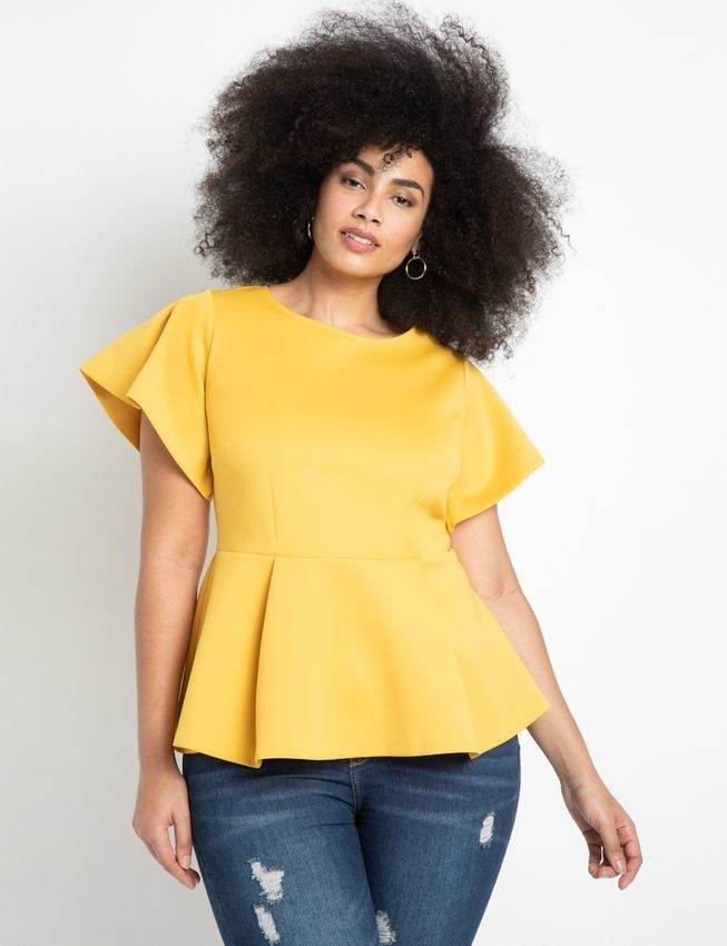 model wearing peplum short sleeve top with jeans