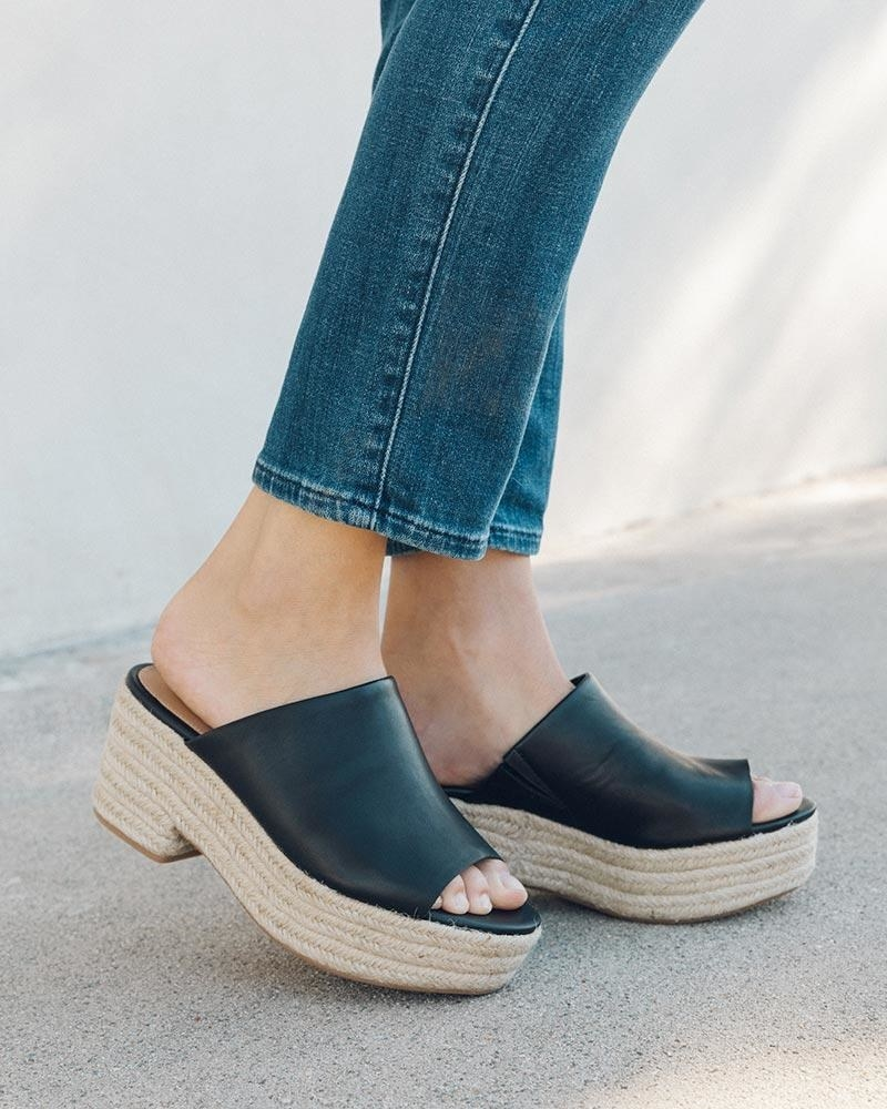a model in black leather upper sandals with a chunky espadrille rope bottom