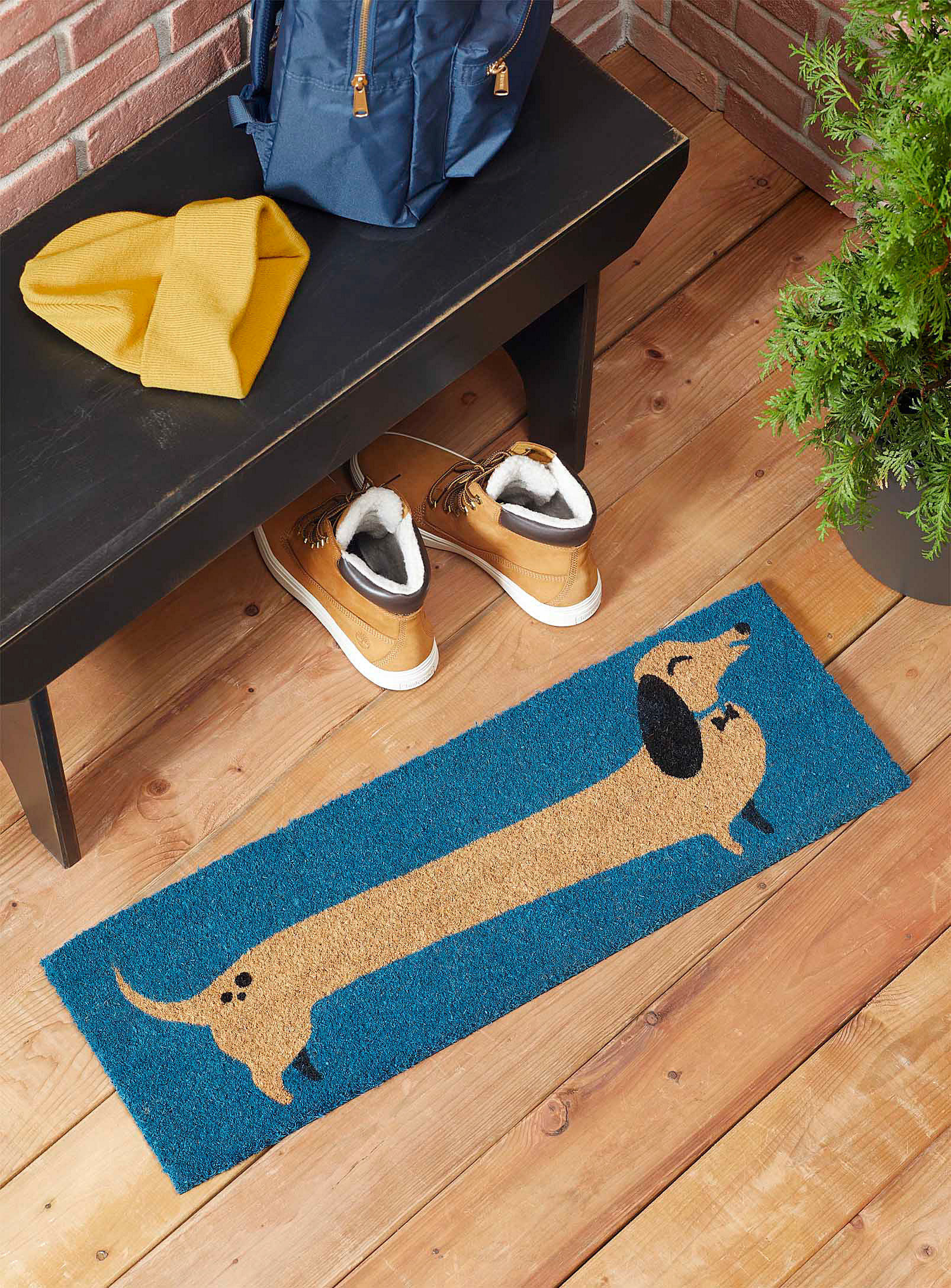 A wide doormat by some shoes with a wiener dog on it
