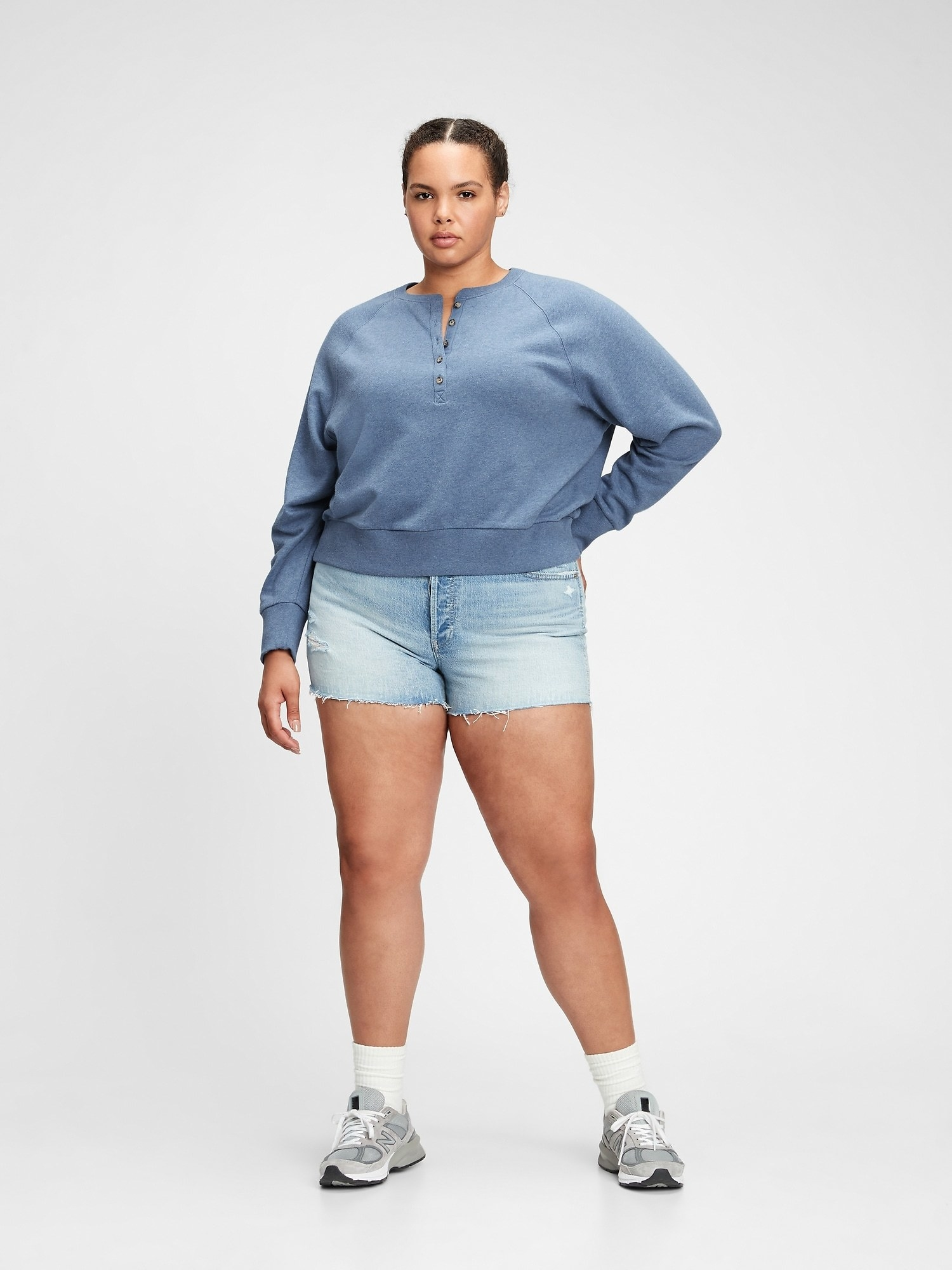 a model in the sweatshirt with buttons down the front in blue