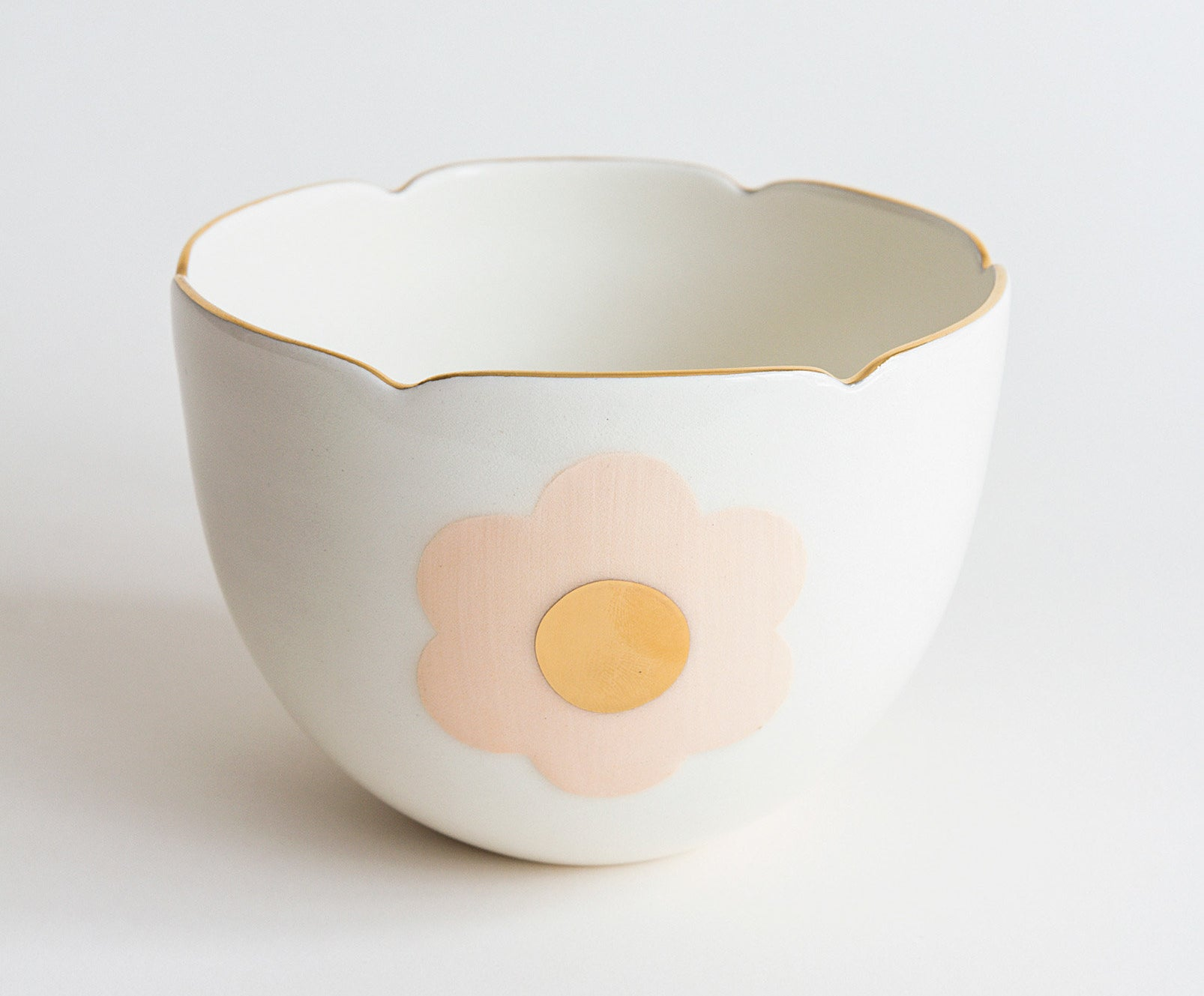 A dainty porcelain bowl with a gold rim and an abstract flower painted on it