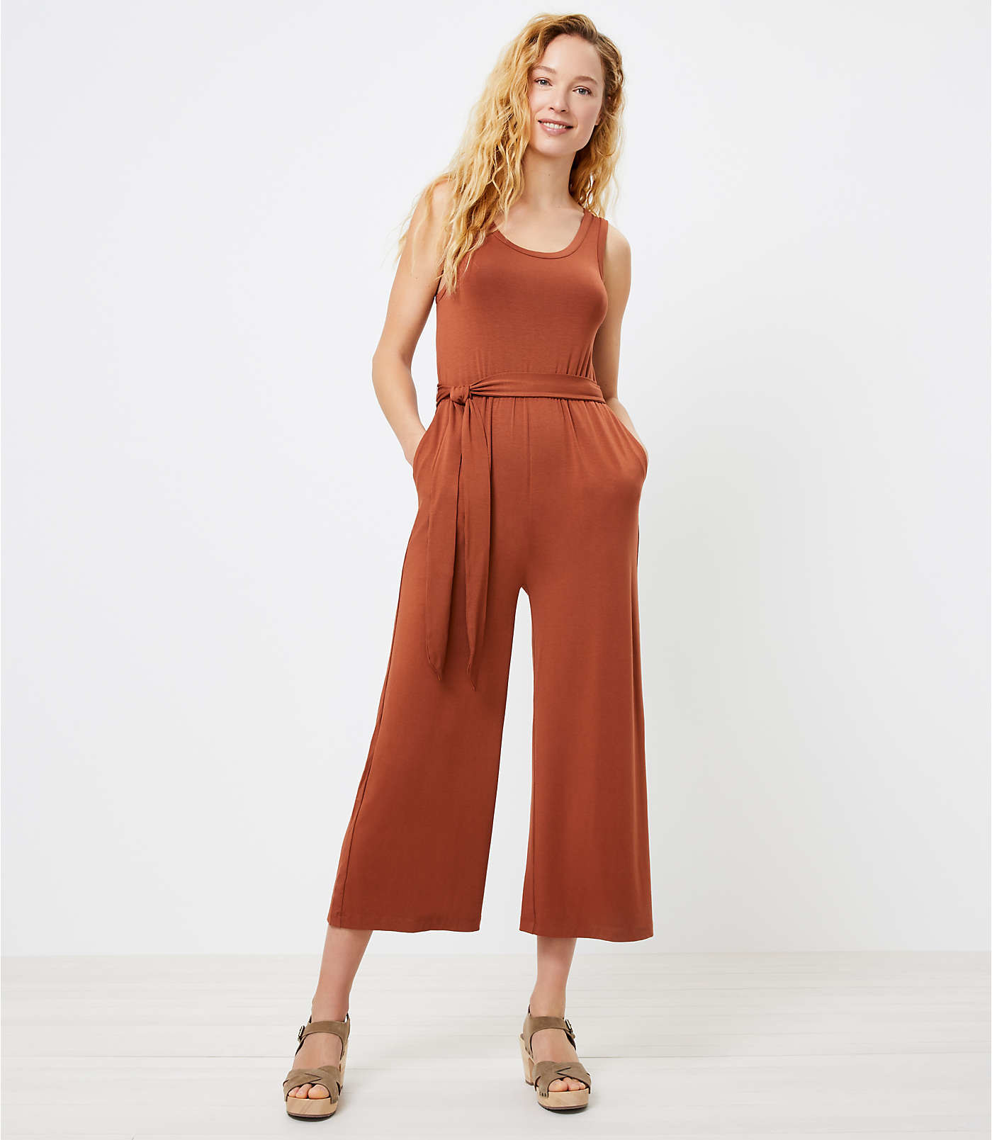a model with their hands in the pockets of a scoop neck burnt orange jumpsuit with a tie around the waist