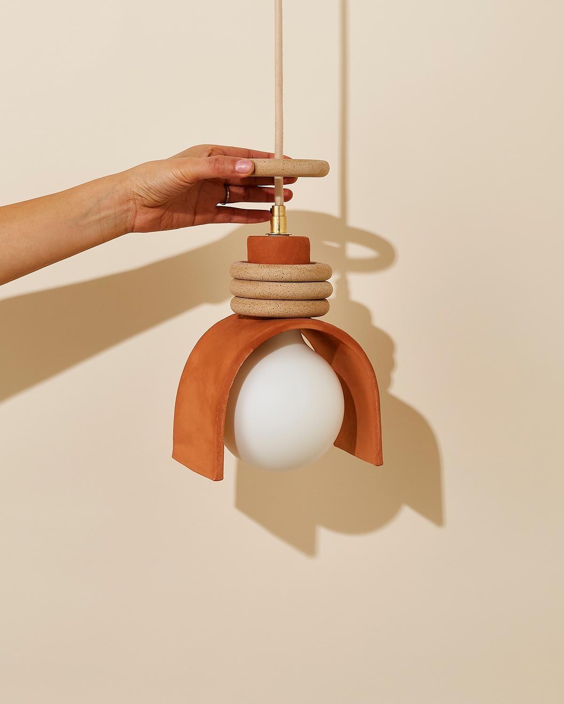 bare bulb pendant with a U shape terracotta piece over the bulb