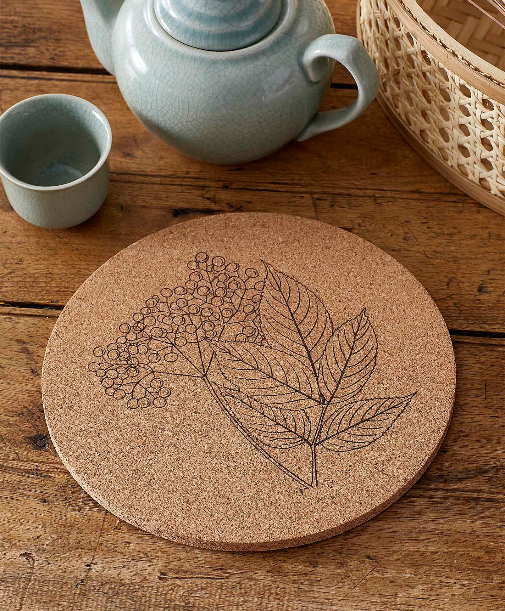 The cork trivet with a floral design on it next to a teapot and a cup