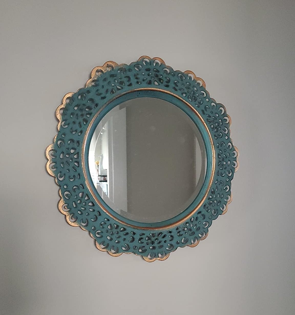 reviewer image of the turquoise stonebriar decorative round metal lace mirror mounted on a wall