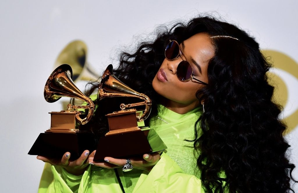 """H.E.R., poses with her awards for Best R&B Performance """"Best Part"""" and Best R&B Album """"H.E.R."""""""