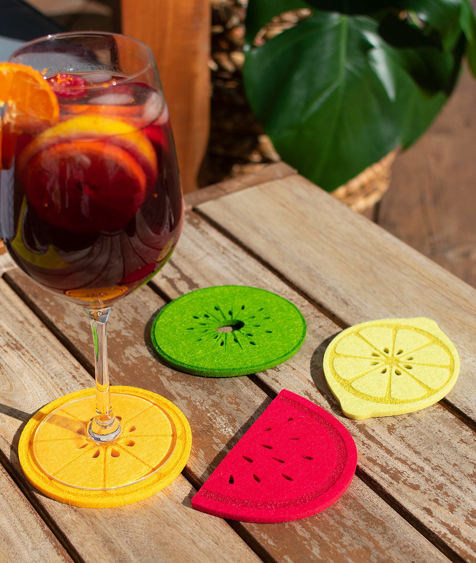 four coasters in the shapes of orange, watermelon, lime, and lemon slices