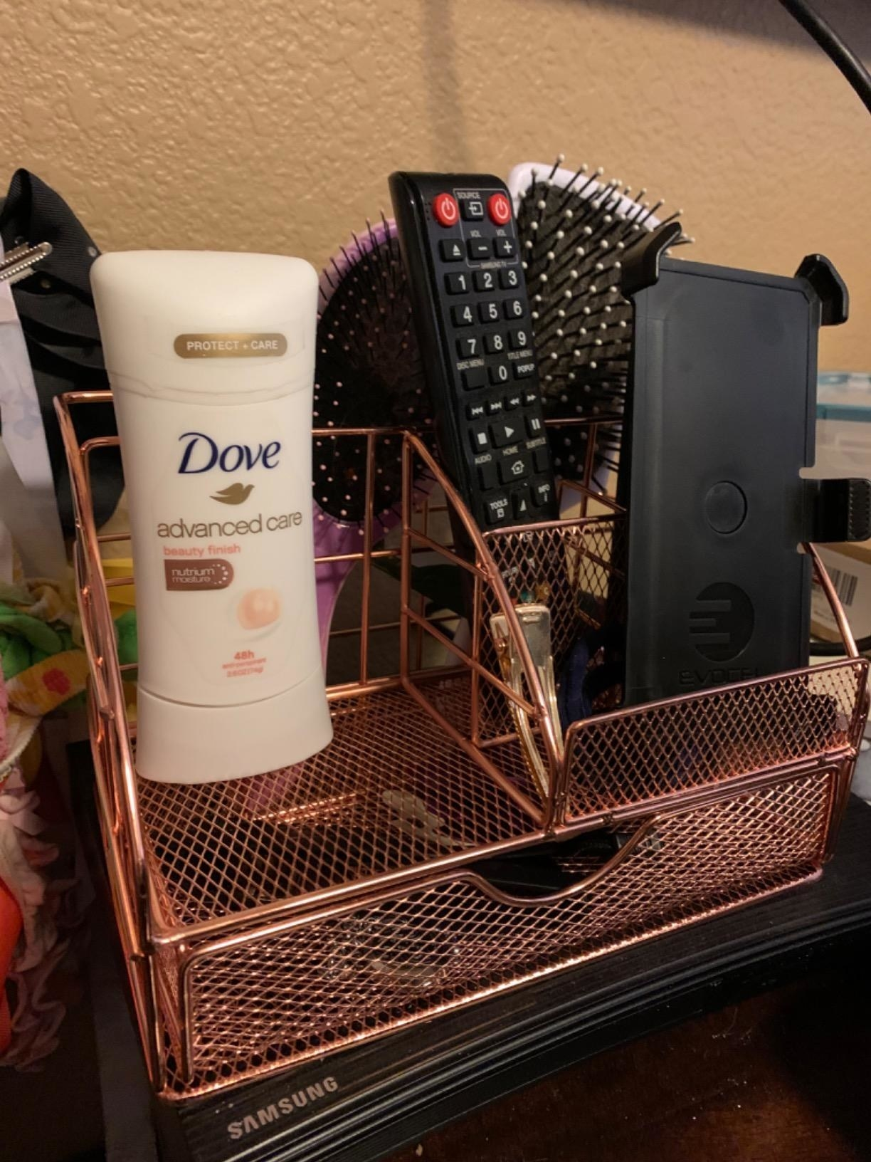 The organizer, which has a small drawer and three holding areas, in rose gold