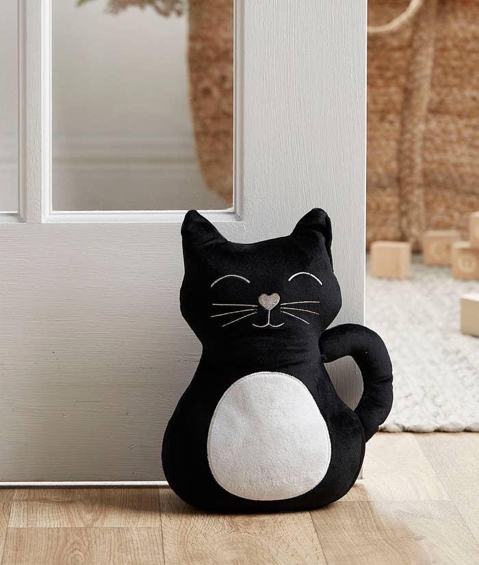 A cat-shaped door stopper holding a door open