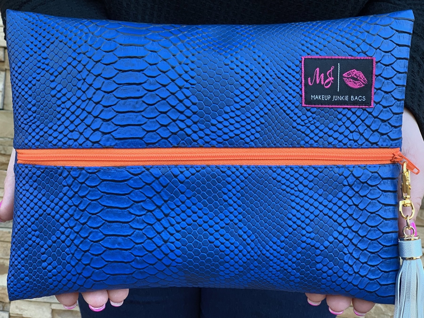 person holding up a Makeup Junkie bag with cobalt blue snakeskin and a bright orange zipper