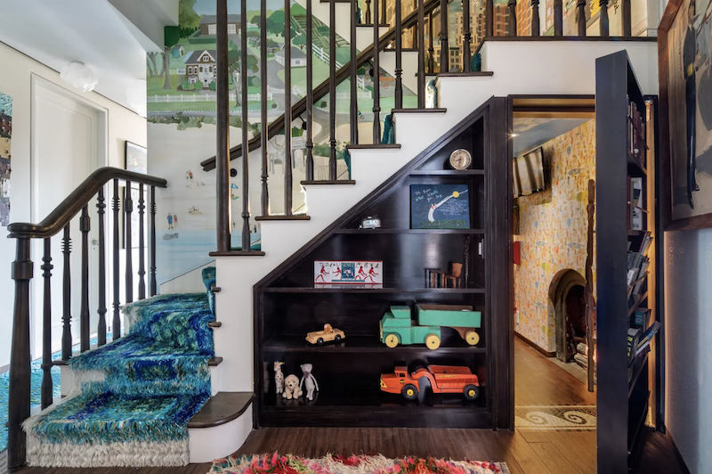 The hidden door is under the staircase which has built-in shelving with knick knacks displayed