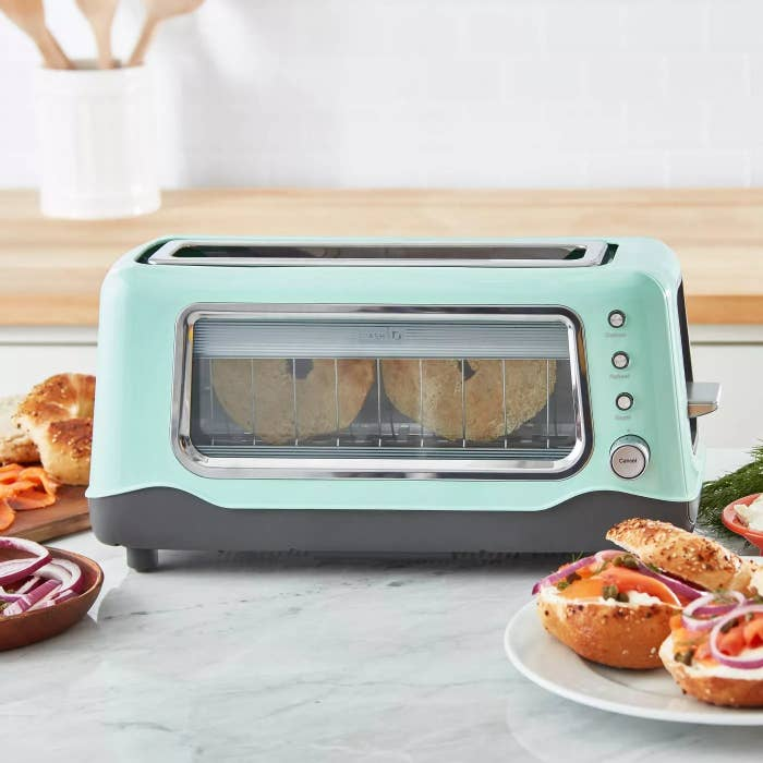 The aqua toaster on the counter with a bagel inside