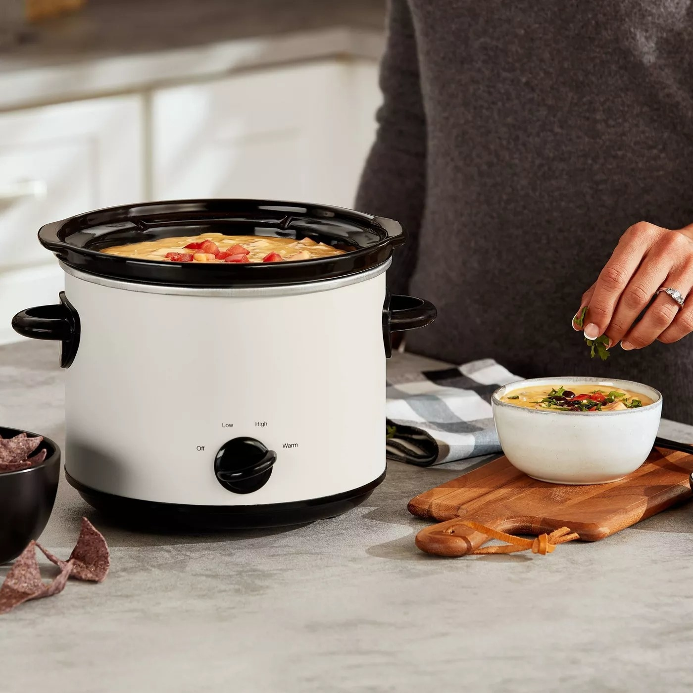 A model making dip using the off-white Crock Pot
