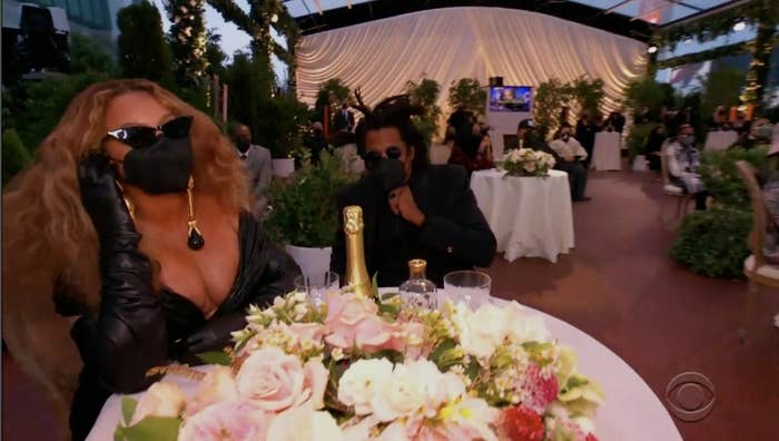 Beyonce sits at a table with sunglasses, a black mask, and long leather gloves on