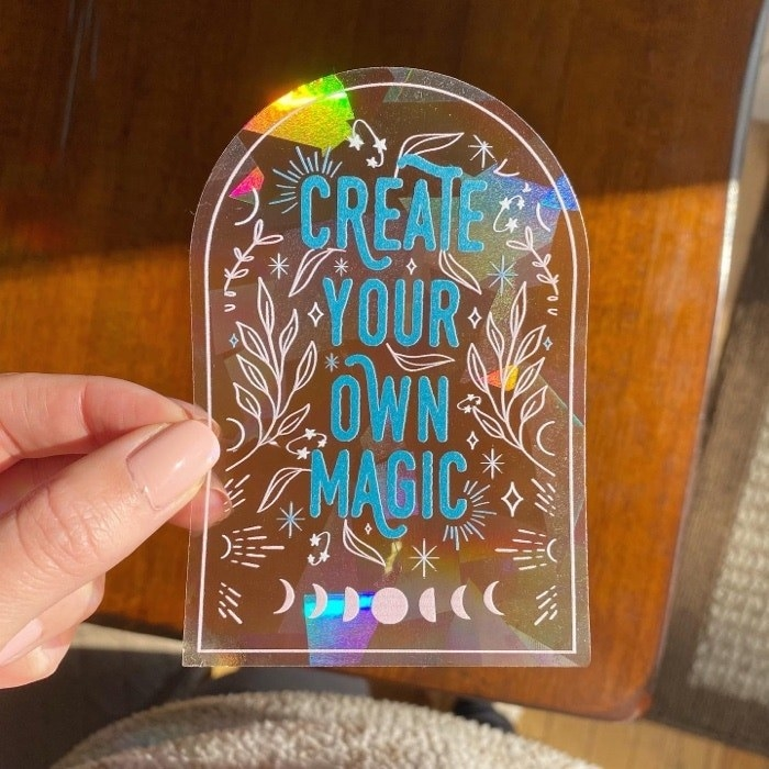 """A hand holding a window decal suncatcher that says """"Create your own magic"""""""