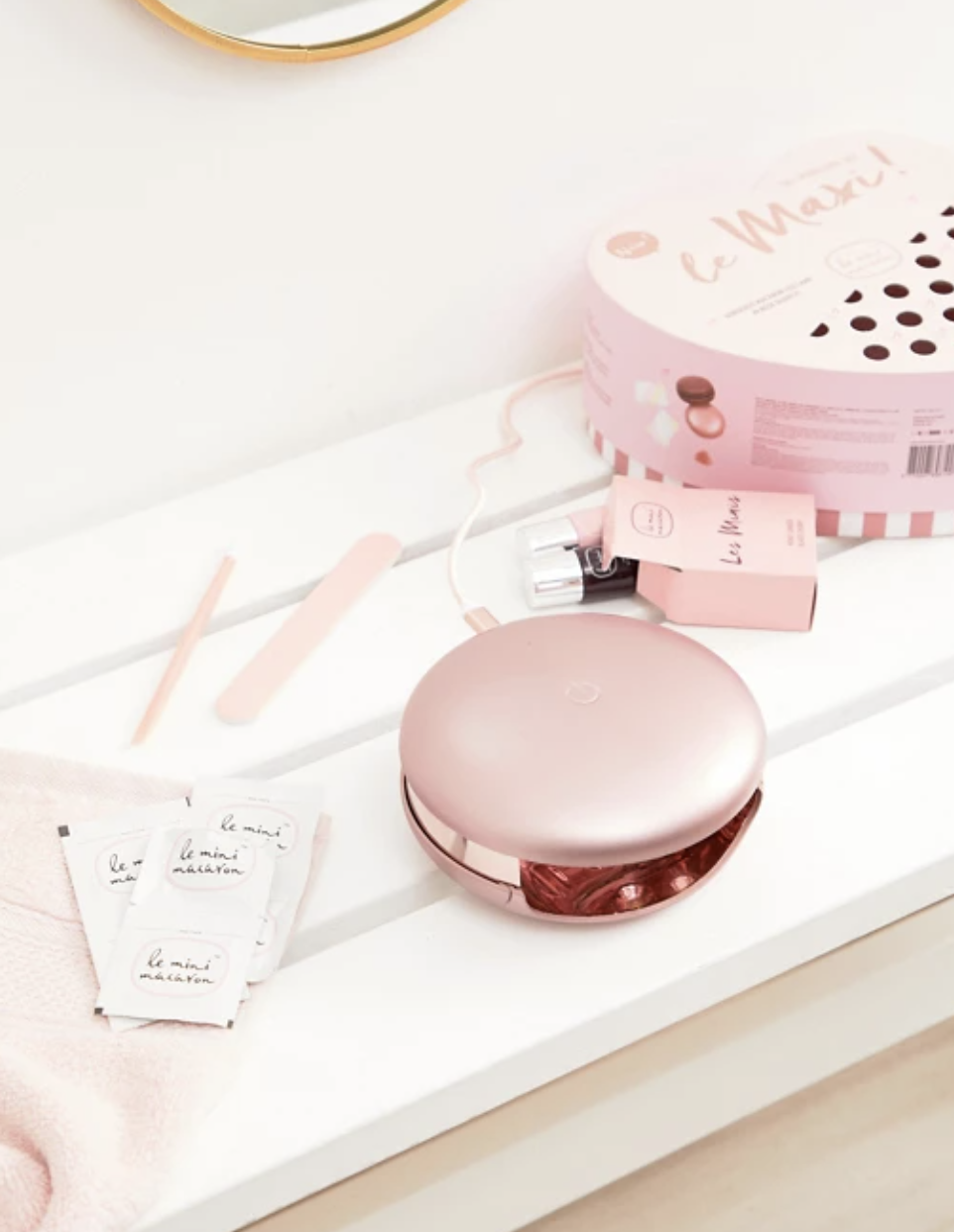 the pink gel manicure kit with a pink LED lamp and two gel nail polishes on table