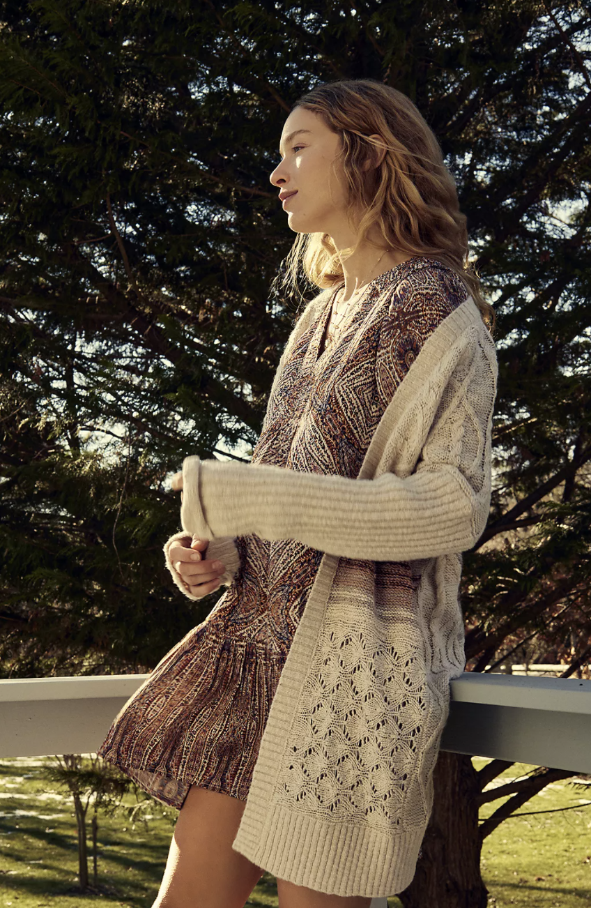 a model in an oversized off white cardigan with various designs woven into it over a dress