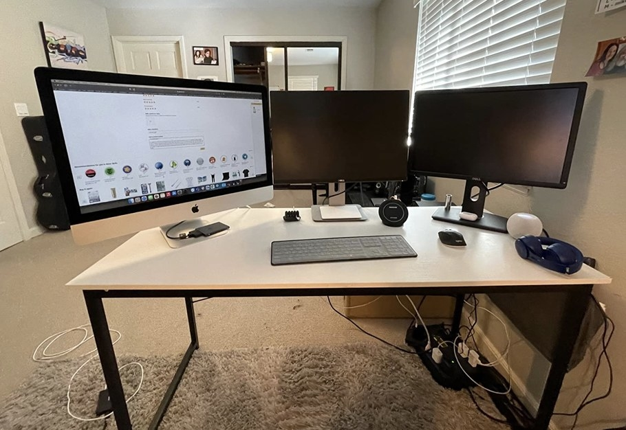 A wood computer desk with metal legs with storage bag on the side